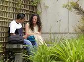 Photo of students sitting on bench in VIU Japanese garden
